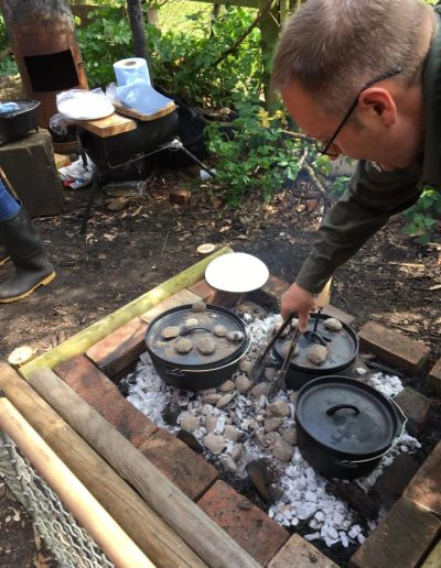 The Bushcraft Man cooking Hot Buns in a Dutch Oven